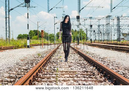 Young beautiful girl in black dress and nylons walking down rail tracks, cargo wagons in background
