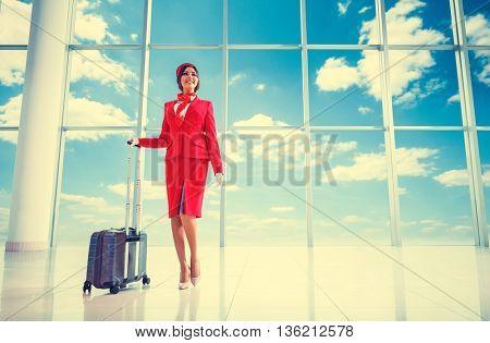Smiling stewardess with suitcase