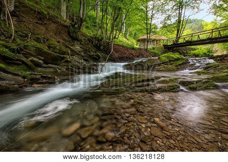 beautiful view of the fuzzy water of a small river with a bridge and a house in the mountains