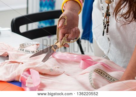Close up view of female dress maker hands cutting something. Dressmaker works at her atelier. Handmade clothes