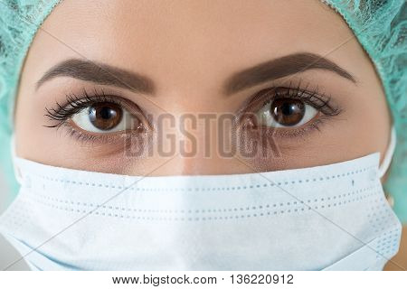 Close up portrait of young female surgeon doctor or intern wearing protective mask and hat. Healthcare medical education emergency medical service surgery or veterinary concept