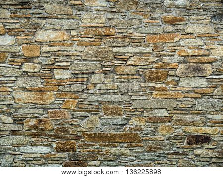 a stone wall protects from view in a garden.