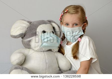 portrait of a sick child in a medical mask with a soft toy.