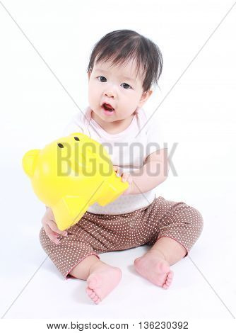 Cute baby with piggy bank on white background