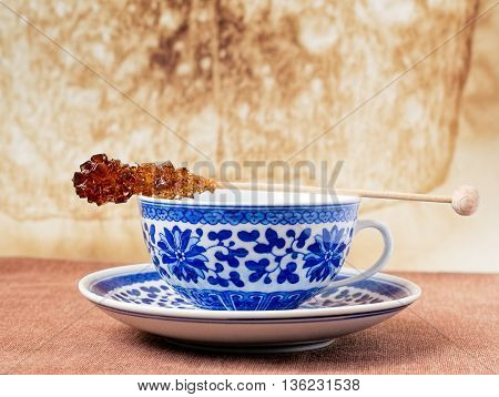 Blue pattern painted vintage cup of tea with brown sugar stirrer on top