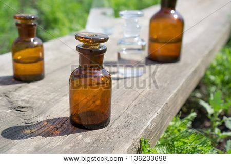 little brown bottles on wooden board and green grass