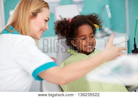 Nice black girl in dental chair showing teeth in mirror to dental female assistant