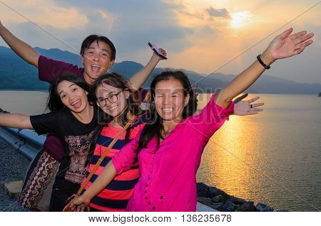 Group of people the family asian tourists are happy during the sunset over the lake at Khuean Sinakharin Dam in Kanchanaburi Province Thailand