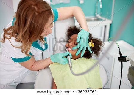 Dental polishing in dental practice to nice black kid