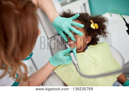 Female dentist polishing teeth to young girl in dental ambulance
