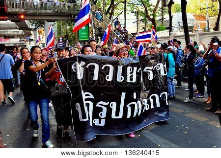 Bangkok Thailand - January 13 2014: Protestors marching along Sukhamvit Road carrying anti-government banner at the Operation Shut Down Bangkok protest *