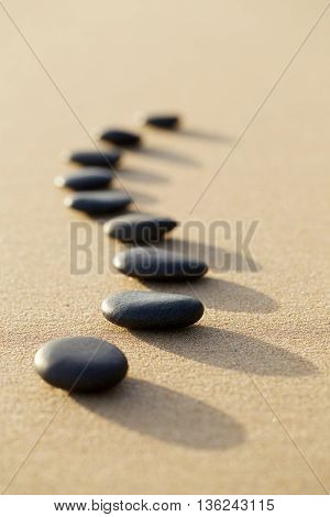 Set Of Hot Stone On White Sand Calm Beach In Backbone Shape. Selective Focus, Spa Concept