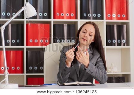 Young businesswoman  does manicure on a workplace in the office. Timeout.