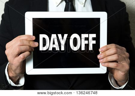 Business man holding a tablet with the text: Day Off