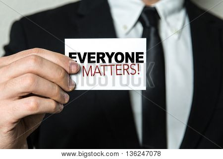 Business man holding a card with the text: Everyone Matters!