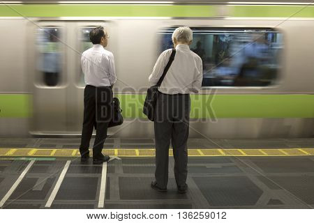TOKYO-JAPAN, 27 June 2016:  Business people waiting for the JR train and fast moving train. It is one of Tokyo's busiest and most important lines in Tokyo, Japan.