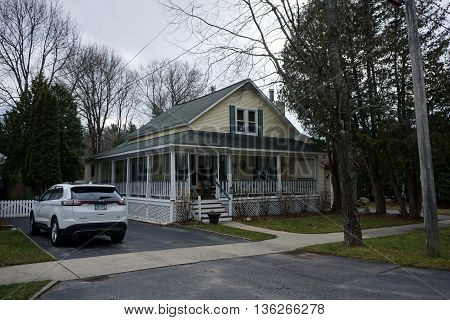 HARBOR SPRINGS, MICHIGAN / UNITED STATES - DECEMBER 24, 2015: A yellow home with a wraparound porch near downtown Harbor Springs.