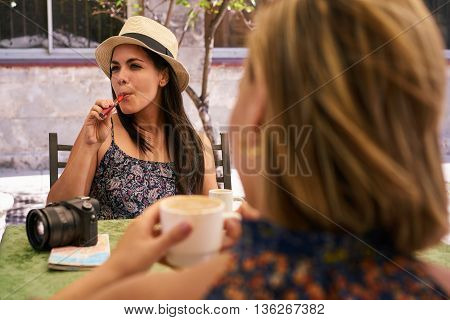 Female friends on holidays people traveling young women having fun on vacation two happy girls smiling in Havana Cuba sitting at bar smoking electronic cigarette in cafeteria talking drinking
