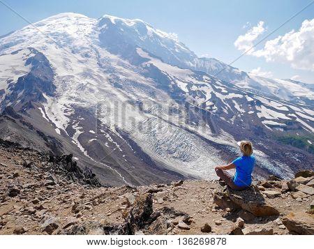 Woman in yoga pose meditating in mountains.  Burroughs Mountain Trail Mount Rainier National Park Seattle Washington USA.