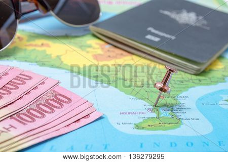 Map of Bali with pin pinned to Kuta area and other travel objects money passport and sunglasses.