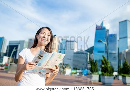 Woman holding city map and looking far away