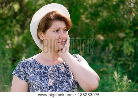 thoughtful Woman in a summer hat on nature