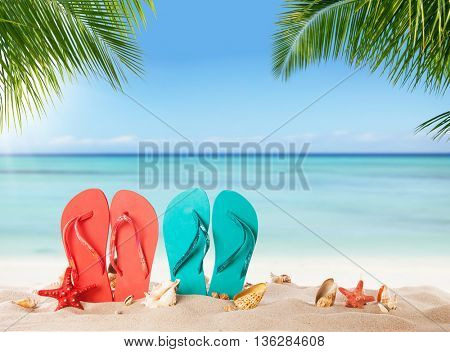 Summer flipflops on sandy beach, blur sea on background. Summer exotic relaxation concept