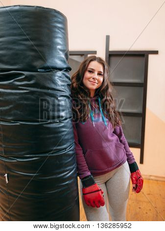 Smiling athletic girl standing near punching bag. Pretty female kickboxer in red boxing gloves relying on punching bag at gym. Looking at photographer cute female kickboxer