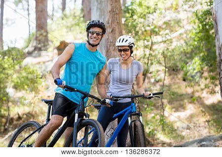Couple smiling and posing with their bikes on the wood