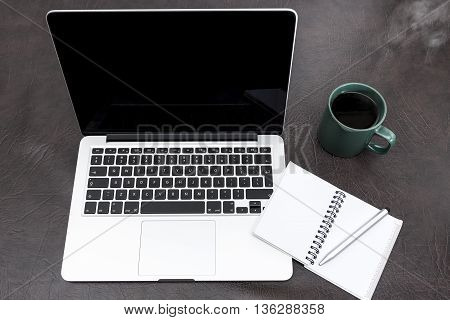 Laptop On A Desk With A Notebook And Steaming Coffee