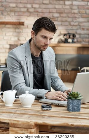 Young businessman sitting at table, working with laptop.
