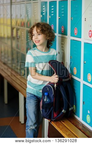 Little learner standing near lockers in school hallway. He put the backpack on the bench and retrieved something from it. The boy somewhere looks.