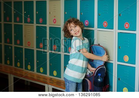 The primary school students standing in the hall near the lockers. The boy somewhere looking. His open backpack on the bench. The guys have a pretty face and curly blond hair.