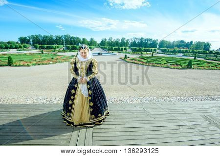 Historical cosplay. Beautiful woman in the similitude of Marguerite of Navarre queen of France ancient dress in the garden near palace poster