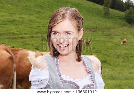 Portrait of an attractive laughing young woman in dirndl standing on a meadow