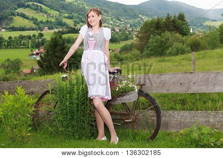 Carefree young woman in dirndl holding on to an old bicycle firmly stands as a plant stand in the garden for decoration. - Horizontal