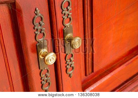 Brass door handles with ornate escutcheons on a wooden cabinet or cupboard with raised panels close up oblique angle view with copy space