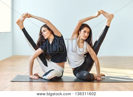 Two Young Women Doing Yoga Asana Compass Pose