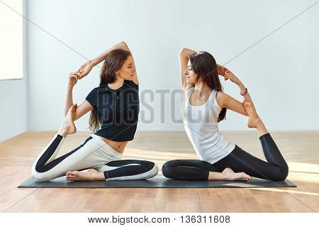 Two Young Women Doing Yoga Asana Eka Pada Rajakapotasana