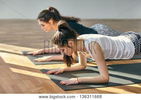 Two Young Women Doing Yoga Asana Low Plank Pose