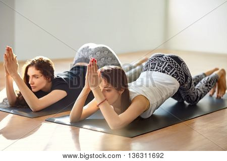 Two Young Women Doing Yoga Asana Eight Limbed Pose Variation