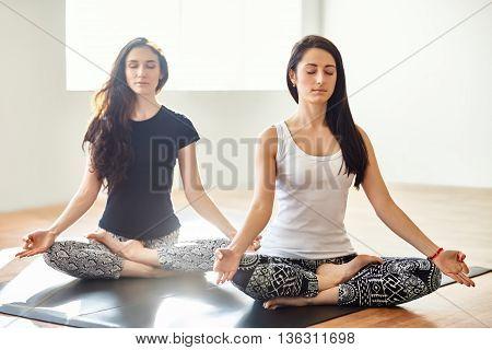 Two Young Women Meditating In Lotus Pose