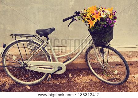 Cute bicycle with a basket full of field flowers near grey wall. Vintage toned