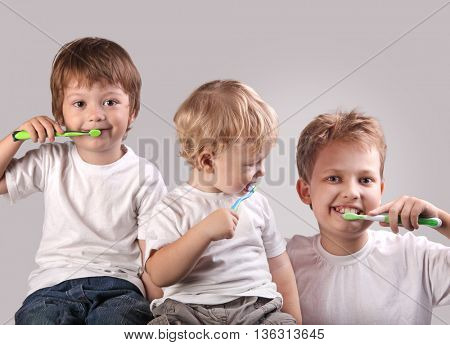 three brothers brushing teeth together