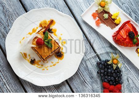 Plates with cake and berries. Blueberry and sliced strawberry. Tasty honey cake and flan. Sweet dishes with decoration.