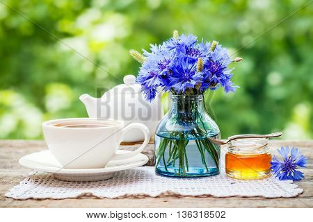 Tea cup teapot honey jar and summer bouquet of blue cornflowers on table outdoors. Summer still life.