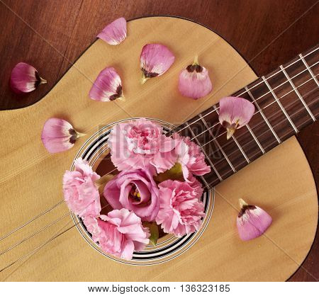 An overhead photo of a guitar with tender pink flowers (carnations and eustomas) and petals