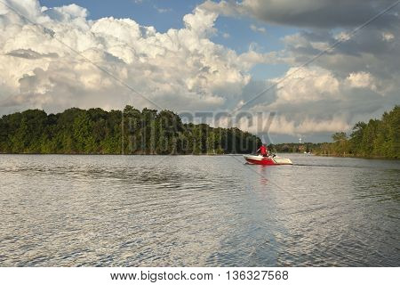 Speedboat heads out onto a Minnesota lake in evening sunlight below dramatic clouds