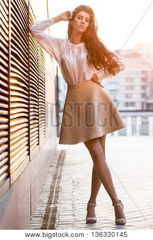Stylish girl with beautiful hairstyle stands with crossed legs on the blurry urban background. She wears a white blouse, beige skirt and beige sandals. Right elbow leans on the lattice and the right hand leans on the head, left hand is on the waistband. S