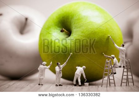 Miniature painters coloring green apple. Macro photo.